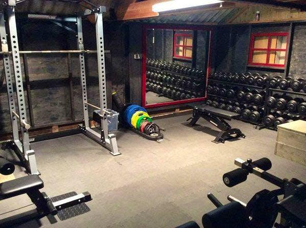 Notare la collezione di manubri e il rack di questa Home Gym ben attrezzata